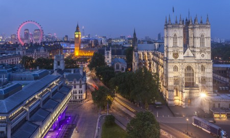 London landmark, Big Ben clock tower and the Houses of Parliament, view from above at dusk. Westminster Abbey and the River Thames. The London Eye in the background.
