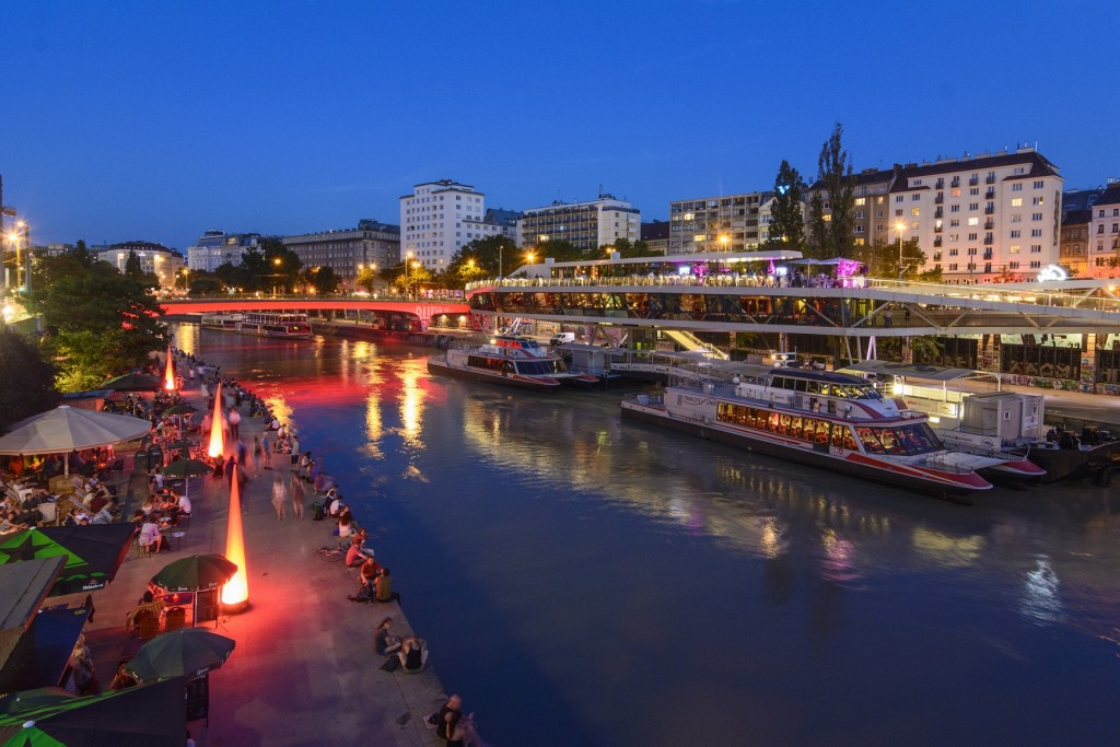 """Donaukanal (Danube Canal) boat station Wien City , excursion boats, ship - restaurant """"Motto am Fluss"""" Shore restaurants, people sitting on seawall"""