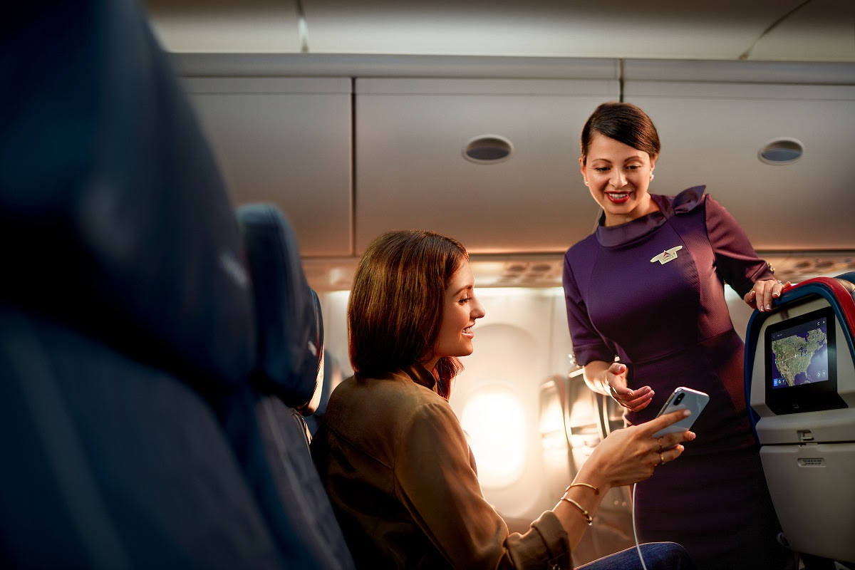 A customer smiles as she shows a flight attendant something on her phone -   License expiration date:  8.31.21 Employee names:  Gabriela Gilbertson Talent names:  Kali Fanelli | These images are protected by copyright. Delta has acquired permission from the copyright owner to use the images for specified purposes and in some cases for a limited time. If you have been authorized by Delta to do so, you may use these images to promote Delta, but only as part of Delta-approved marketing and advertising. Further distribution (including providing these images to third parties), reproduction, display, or other use is strictly prohibited.