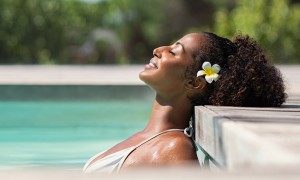 Young black woman relaxing at spa pool with frangipane flower in the hair. Beautiful young woman relaxing in outdoor spa swimming pool with head leaning at poolside. Closeup face of attractive black girl with closed eyes enjoy vacation at resort.